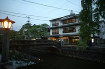 川沿いに本館を眺む(夕暮れ時)