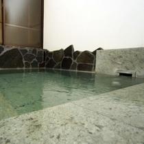 伊豆石が眩しい天然温泉の内湯