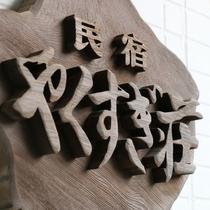 【民宿 やくすぎ荘】屋久杉を使った看板。看板をバックに旅の思い出の一枚を!