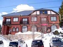 雪の中の赤レンガの重厚なホテル