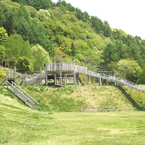 *【芝生遊具公園】なだらかな芝生丘陵に木製アスレチック遊具を設置した公園