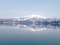 田沢湖に映える、雪が積もった逆さ秋田駒ヶ岳