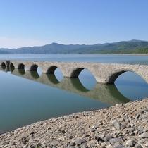 透き通った湖面にうつるアーチ型の橋がまるでメガネのようなタウシュベツ川橋梁