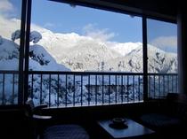 冬の8畳のお部屋からの景色。真っ白な雪景色と北アルプスを眺めながら、温泉を使った暖房で暖かいお部屋で
