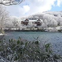 *外観(冬)/雪と、ドッコ沼と、当館の美しいコントラスト。