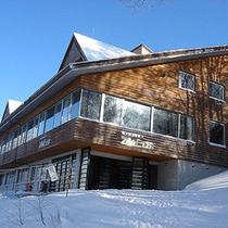 *外観(冬)/降り積もる雪の中、静かに佇む当館。