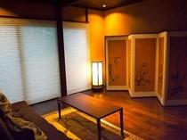 庵 さき玉屋町町家 1Fリビング 2人掛用のソファと屏風が設えてあります。