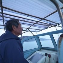 「まつみや丸」に乗る主人。現役漁師の宿です