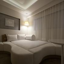 大きなベッド白を基調にした落ちついた雰囲気の客室