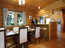 大きな窓から見える森林の緑が美しいダイニングルームとカウンターテーブル、オープンキッチン