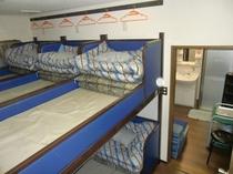団体室の連結ベッドと壁掛けテレビ