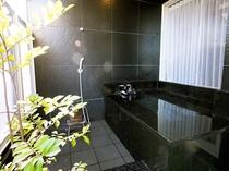 【スイート】黒御影石造りの露天風呂。半身浴を楽しめるよう、浴槽内に腰掛けられるようになっています。