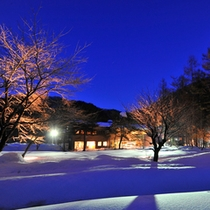 【冬】真っ白な雪景色の中、月明かりに照らされる宿風景。雪見風呂も楽しめる季節、夜の露天風呂も趣がある