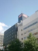 セブンイレブンの交差点にて、左手に見えるグレー色のビルがアパホテルTKP札幌駅前でございます