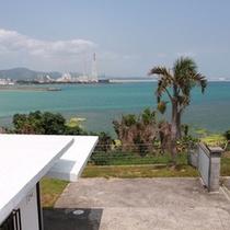 入口スロープより、庭越しに海を望む風景