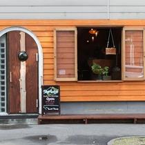 オレンジ色の木製の壁が目印です。