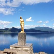 *【周辺】たつこ像の姿は、澄んだ青い湖水に映え、神秘的な佇まいを見せています。