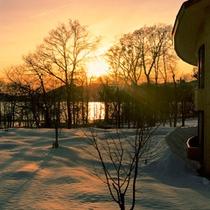 *【夕焼け空と田沢湖(冬)】夕焼けに照らされた湖面と雪のじゅうたんが幻想的な風景をつくります。