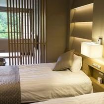 【エグゼクティブルーム】格子仕切りの寝室。シックなインテリアが安らぎの空間を演出します。