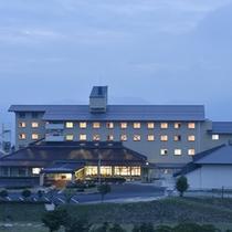 【外観】夕暮れの空に浮かび上がるように建つ高台にある当館。