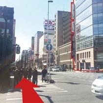 【道案内3】ガラス張りの大きなビル(1Fはみずほ銀行)を目印に横断歩道を渡ります