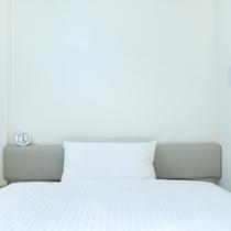 コンパクトながら、ベッド幅はゆったり130cmのシングルルーム。専用シャワー/トイレ付き。