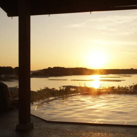「朝なぎの湯・夕なぎの湯」の庭園露天風呂(女性)からのぞむ英虞湾 ※写真は冬(夕日が見られる期間)の景色です。 写真提供:楽天トラベル