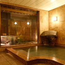 """本館女湯/御影石、インド砂岩などの自然石を施した大浴場。美肌の湯""""湯の川温泉""""源泉かけ流しです。"""