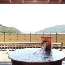露天付客室「風人」の鋳鉄製の露天風呂です。垣根の向こうには湖が。