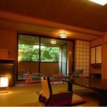 窓に広がる緑の中、贅沢な檜露天風呂付き客室