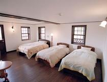 26畳のトリプルルームにはシモンズベッドのクィーン1台とシングルが2台