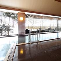 開放感のある窓の外に雪景色が広がる内湯