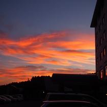 サンセット 橙色に染まる当館と駐車場