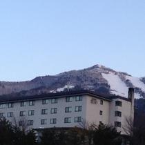 冬の当館とすぐ裏のよませ温泉スキー場(高社山)