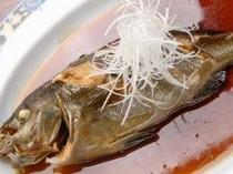 16. 片時も鍋から離れず煮汁をまわしかけ仕上げる煮魚は繊維も見えないほどにふっくら(素材は日替り)