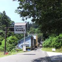 【温泉街】こちらからの松之山温泉の看板の先をほどなく行くと玉城屋です。左手に当館が見えてまいります。