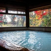 【丸太造りの温泉浴場】乳白色の温泉にのんびり入りながら、秋は赤や黄色に色づく紅葉を眺める贅沢な時間