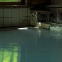 【丸太造りの温泉浴場】乳白色の温泉が溢れ、古き良き湯治場の雰囲気を残した内風呂