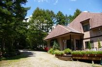 夏の森に佇むバーク外観、広い敷地に感動すきに駐車ください
