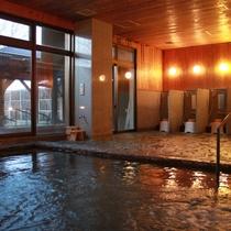 【峰の湯 内風呂】個別に仕切られた洗い場で気兼ねなくご利用いただけます。地元の三波石を使用しています