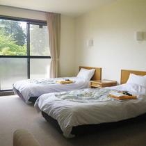 *【2階/洋室ツイン一例】ソファ+テーブルセットも配置されたゆったりとした広さの客室。
