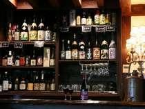 炭火ハウス/焼酎棚【食事処】囲炉裏の食事処には、全国から選りすぐられた焼酎や酒が揃う/例