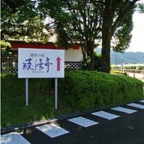 【酒泉の杜 綾陽亭】へはこの看板よりお入りください。バス駐車場を抜けると、宿泊者専用駐車場です→