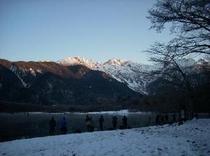 晩秋の雪の上高地大正池の朝焼け
