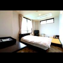 和洋室のお部屋。セミダブルのベッドと3畳のスペースがあります。