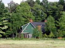 牧草地に佇むアーリーアメリカンの緑の館
