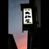 薄暮に映る「大和屋」の看板。どことなく懐かしさを感じるレトロな宿でくつろぎのときをお過ごしください。