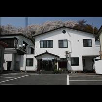 山々に抱かれた当館は蔵のような白い外観が目印です。心よりのおもてなしをご用意してお待ちしております。