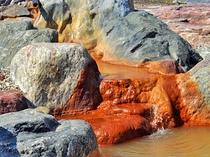 【女湯・露天】湧出口は、温泉成分で赤く染まっています。