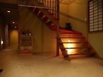 ロビーから2階へあがる階段。浴室へつながる廊下。